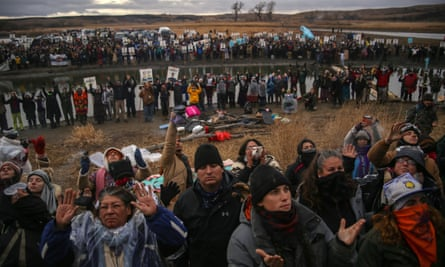 Anti-pipeline protesters raise their arms during a prayer at the Standing Rock reservation in North Dakota.