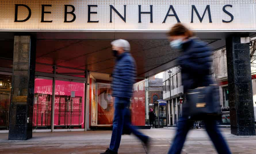People wearing protective masks walk past a Debenhams store in Oxford Street, in London, January 2021.