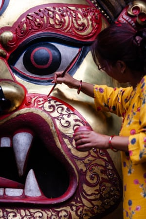 A woman applies finishing touches to a statueof Swet Bhairab