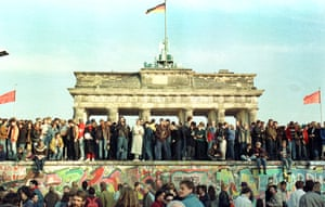 Germans on top of the Berlin Wall in front of the Brandenburg Gate on 10 November 1989.
