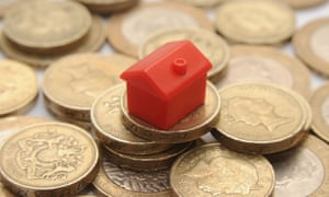 plastic model of a house on a pile of one pound coins