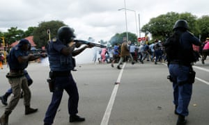South African riot police fire rubber bullets during clashes between South African and foreign national protesters on Friday.