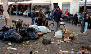 A man looks at a pile of rubbish in a market area of central Rome.