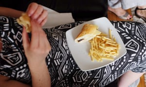 A pregnant woman tucks in to a plate of chips