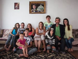 Klinton Bajgora, 13, sits between his parents for a family portrait at home in Podujevo, Kosovo