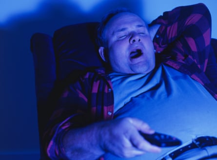 Man sitting in armchair yawning, watching television in darkened living-room