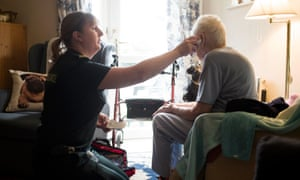 A patient has her temperature taken during a home visit