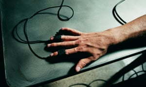 Person's hand hooked up to polygraph test, lie detector close-up (Overhead view)
