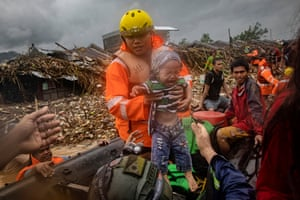 A rescuer carries a baby as floodwaters rise in a submerged village in Rizal province. Tyhoon Vamco has battered the Philippines, causing widespread flooding and destruction in areas still reeling from the effects of Super Typhoon Goni