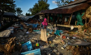 A woman clears debris from her house in Palu, Indonesia after the recent tsunami