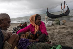 Refugees comfort the elderly woman on the shore.