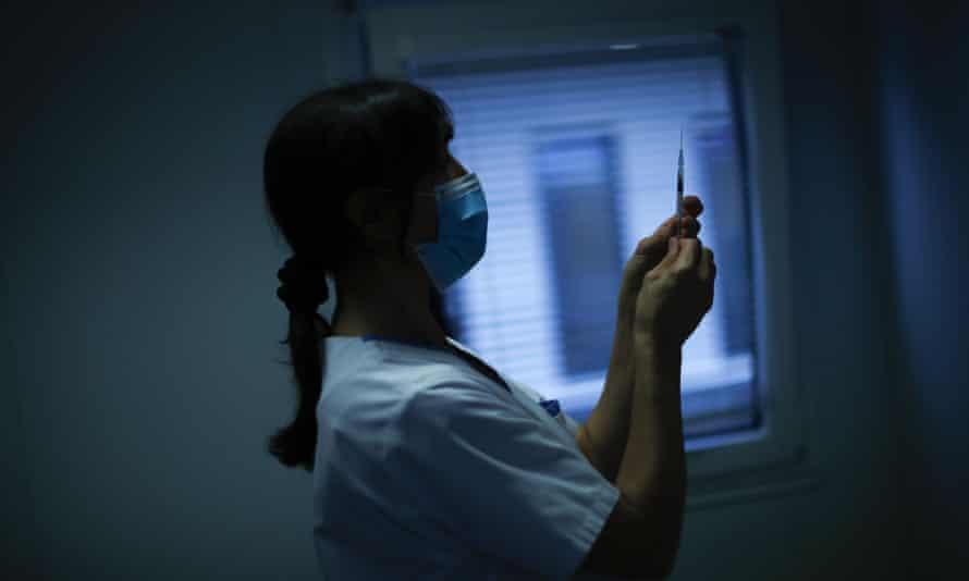 A nurse prepares a syringe with Pfizer/Biontech COVID-19 vaccine