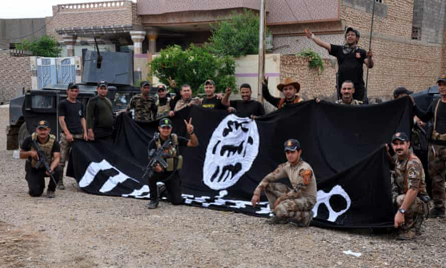 Iraqi soldiers hold an Isis flag after they gained control of the city of Heet in western Iraq after days of fierce clashes.