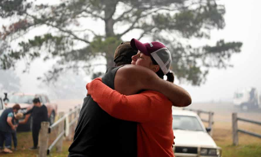 John Aish (L) who lost his home in the New Year's Eve bushfire is hugged at the Cobargo evacuation centre.