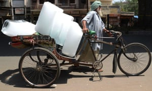 A man uses a rickshaw to transport ice from a factory in Amritsar