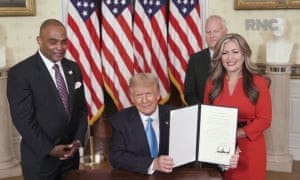 Donald Trump shows a pardon he signed for Jon Ponder, who stands with his wife, and former FBI agent Richard Beasley.