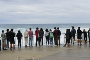 A crowd gathers to watch the huge swell at Bronte Beach.