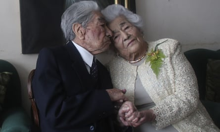 Julio Mora Tapia, 110, and Waldramina Quinteros, 104, sitting close together and holding hands