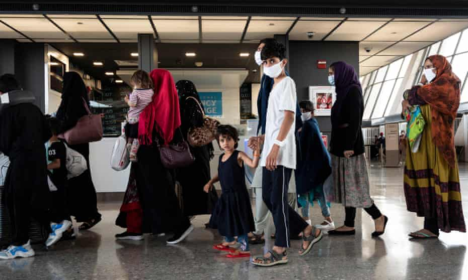 Refugees from Afghanistan are escorted to a waiting bus after arriving at Dulles international airport in Virginia, US