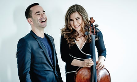 Alisa Weilerstein, holding her cello, and Inon Barnatan stand against a white studio background, laughing