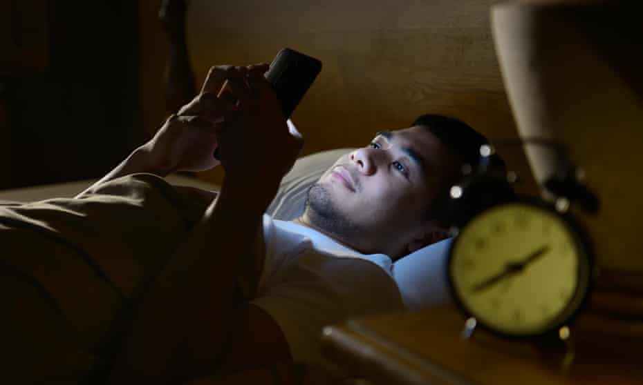 A young man using a smartphone in bed. Banning technology in the bedroom is one tip from sleep expert Vicki Culpin.