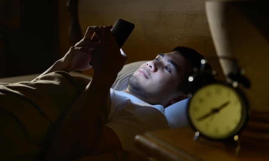 Young man using a smartphone in his bed at night