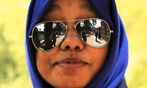 Hamsaa, 22, wears reflective sunglasses as she poses for a picture outside her classroom at the Sudan University of Science and Technology in Khartoum, Sudan