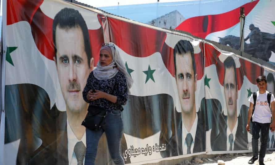 People walking past campaign billboards of Bashar al-Assad