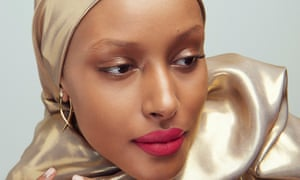 Shahira Yusuf with bright red/pink lips, a gold scarf around her head and shoulders