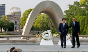 Barack Obama and Shinzo Abe walk after laying wreaths in front of a cenotaph to offer prayers for victims of the atomic bombing in 1945 at Hiroshima Peace Memorial park.