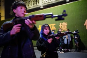 People play with toy guns outside a bar at night, almost a year after the global outbreak of the coronavirus disease in Wuhan.