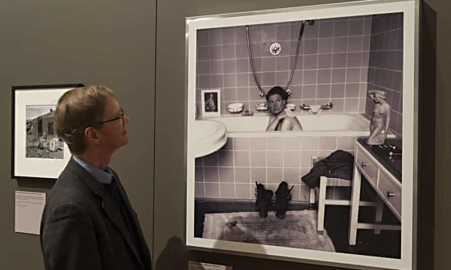 Tony Penrose in front of a photograph of his mother in Hitler's bath, taken in April 1945, and currently on show at Lee Miller: A Woman's War at the Imperial War Museum, London