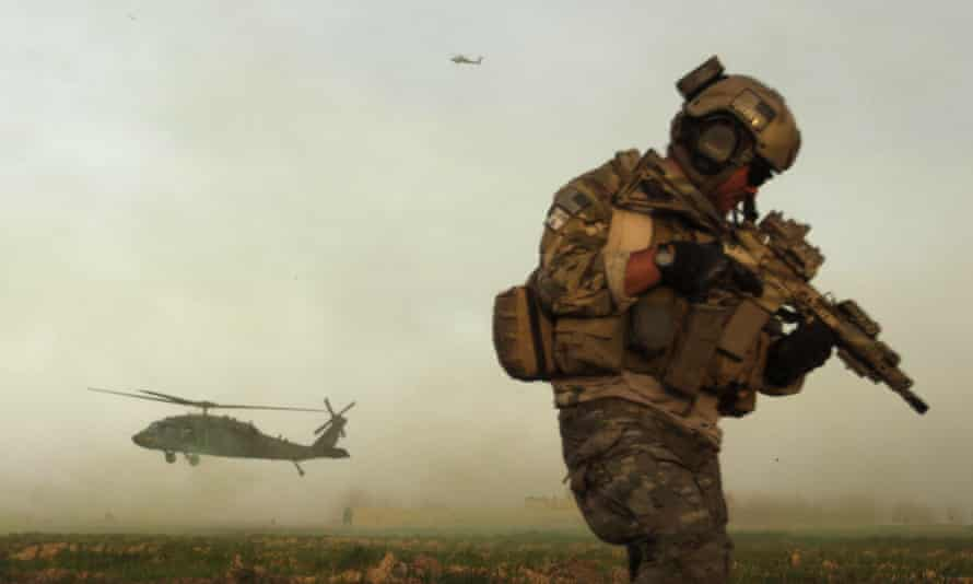 A US army special forces soldier takes cover as a Blackhawk helicopter lands in the Afghan town of Marjah.