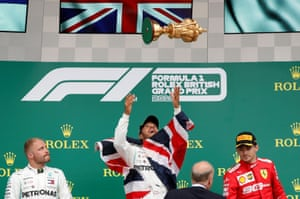 Hamilton throws the trophy in the air as he celebrates winning the race.