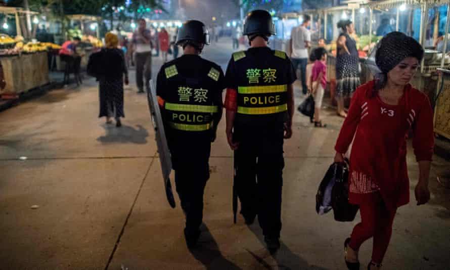 Police in Kashgar, in China's Xinjiang Uighur autonomous region, patrol a night food market