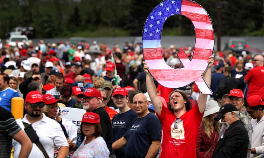 A man holds up a large 'Q' sign while waiting in line to see Donald Trump at a 2018 rally in Pennsylvania.