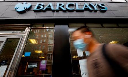 A pedestrian wearing a face mask walks past a branch of a Barclays bank