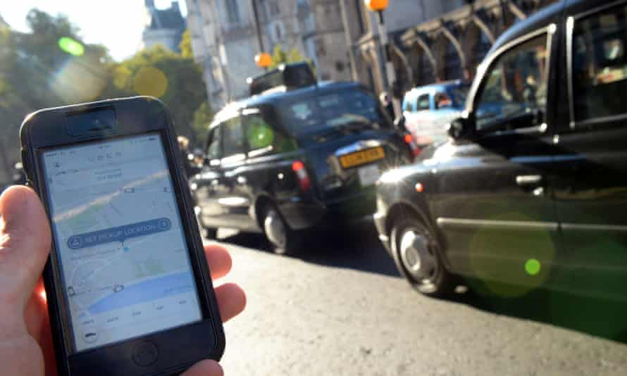 Uber app open on a phone next to line of black cabs