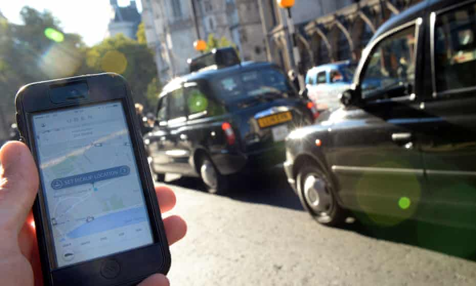 An Uber customer uses the phone app at a black-taxi rank in London.