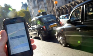 A man holds a smartphone displaying the Uber app in front of London black taxis