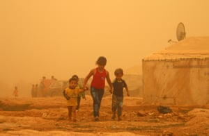 Syrian children walk through a sandstorm at a refugee camp on the outskirts of the eastern Lebanese city of Baalbek