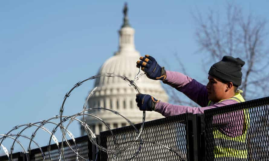 A worker removes razor wire from the top of security fencing on 20 March 2021, as part of a reduction in heightened security measures taken after the 6 January attack on the US Capitol in Washington DC.