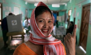 A woman shows her ink-marked finger after casting her vote in Jorhat district of Assam