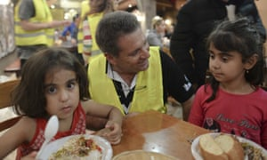 Children receive a free meal at a restaurant on the island of Kos.