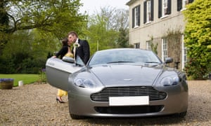 Couple kissing by an Aston Martin outside a country house