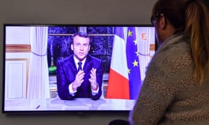 A woman watches Emmanuel Macron delivering his new year's speech on television.