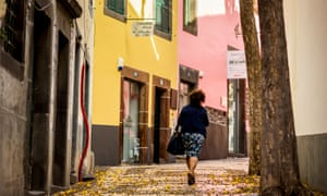A woman walking uphill on the narrow Rua da Conceição, past houses painted yellow and pink, and with yellow flowers fallen from a tree scattering the pavement
