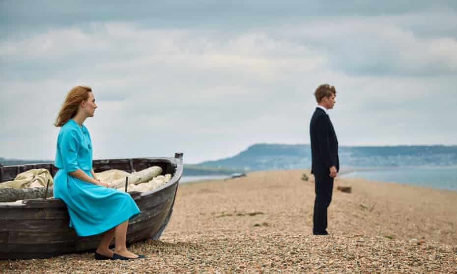Saoirse Ronan as Florence and Billy Howle as Edward in the film On Chesil Beach. They stand looking out to sea on the beach. Dorset, UK.