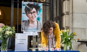 A woman signs a book of condolence after a vigil at Belfast City Hall in memory of Lyra McKee.
