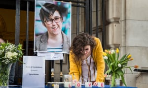 A woman signs a book of condolence after a vigil at Belfast City Hall in memory of the journalist Lyra McKee
